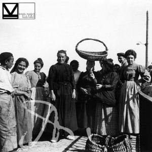 """Sardineras posando. La cesta para el transporte y venta asentada sobre la cabeza, en el suelo una cesta más grande, denominada """"milloi"""", utilizada para descargar la pesca de la embarcación al muelle."""